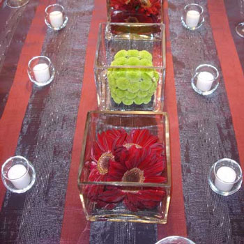 Multiple short square vases centrepiece a long wedding table