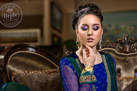 Bold purple eye makeup on Pakistani bride wearing blue and gold lehenga and green dupatta